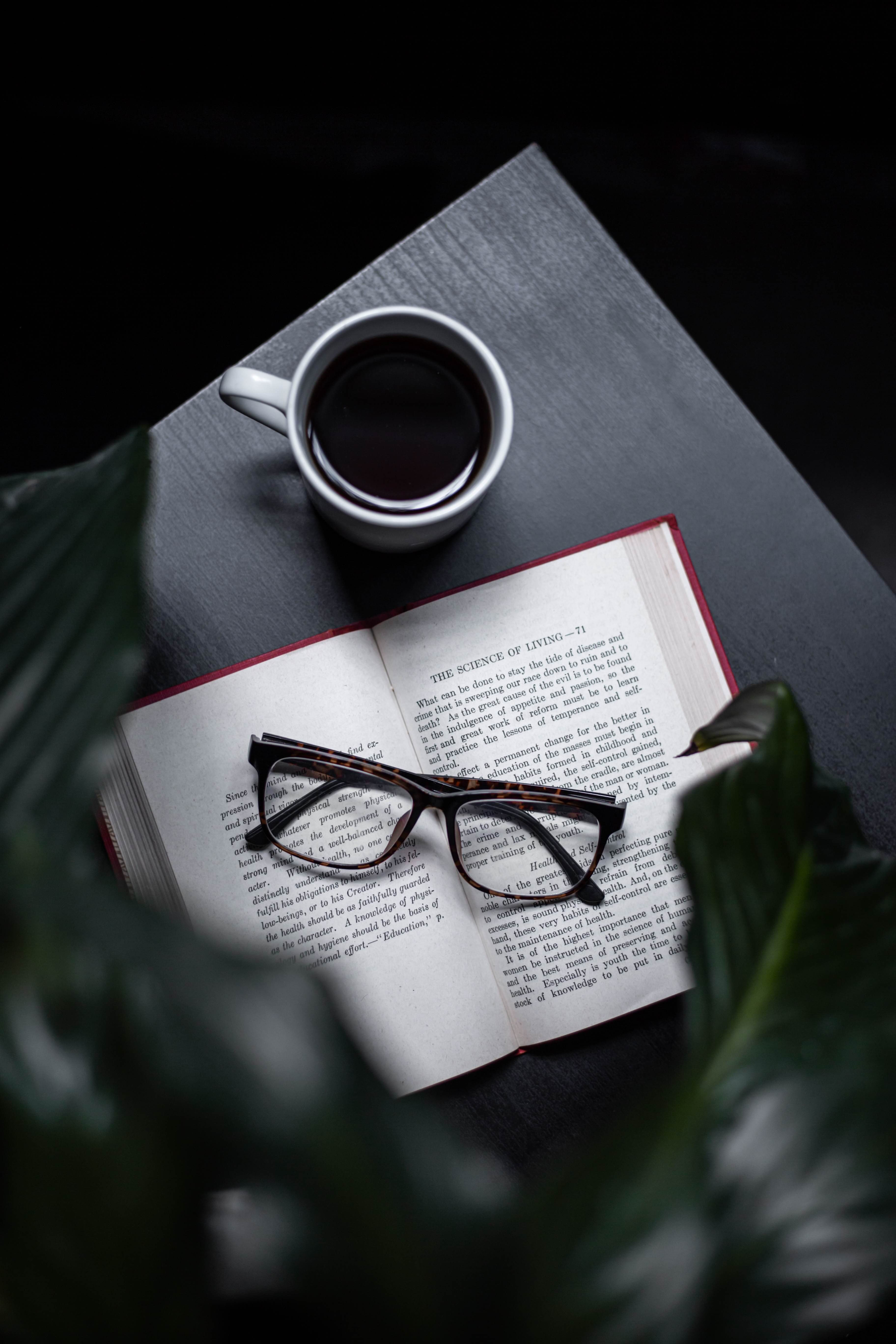Open book with coffee cup on table